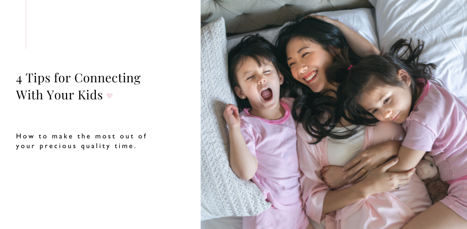 Mother and two daughters cuddling and laughing in bed